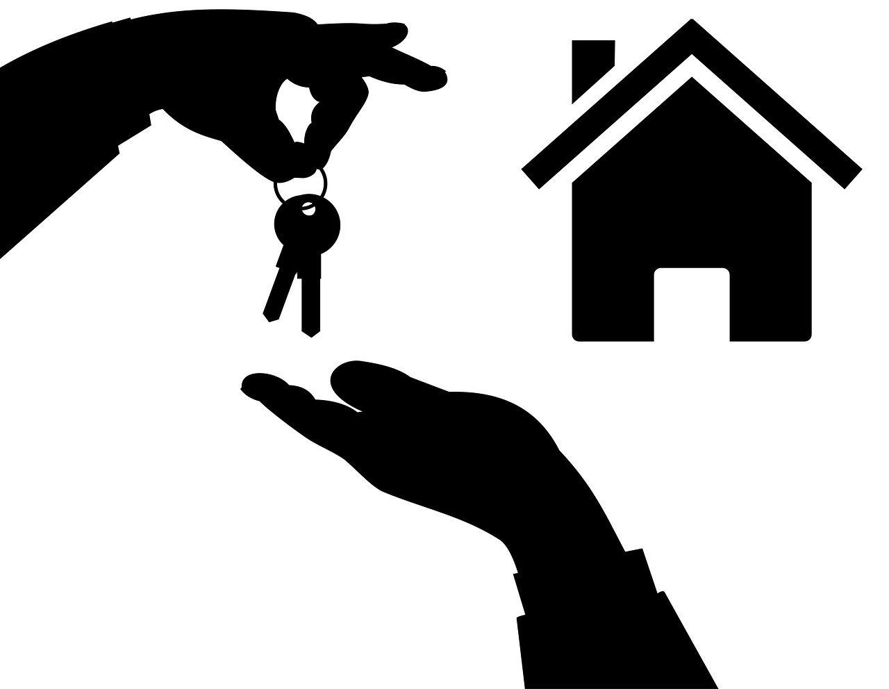 Manos entregando llaves de una casa. Compraventa con reserva de dominio